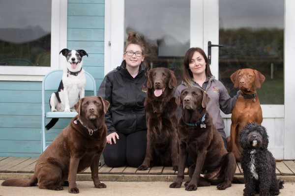 Two female team members kneeling in front of windows outside, smiling at camera with 6 dogs sitting and facing the camera.